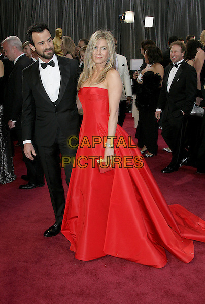 Justin Theroux & Jennifer Aniston (wearing Valentino).85th Annual Academy Awards held at the Dolby Theatre at Hollywood & Highland Center, Hollywood, California, USA..February 24th, 2013.oscars full length black tuxedo white shirt bow tie beard facial hair red strapless dress gown couple engaged silver clutch bag.CAP/ADM.©AdMedia/Capital Pictures.