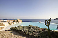 The garden leads down to the infinity pool that has its own man-made beach and spectacular views over the Aegean sea