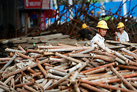 Workers sort out a pile of steel pipes for scaffolding under an highway construction site in Shanghai, China..