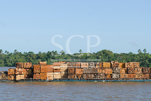 Pará State, Brazil. The Amazon River; barge laden with illegal timber from indigenous reserves in the rainforest.