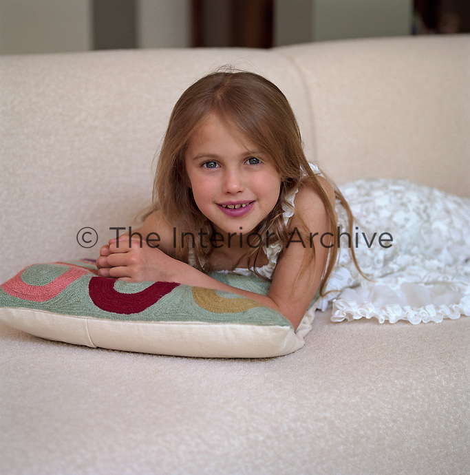 Katarina reclines on the large cream sofa in the living room