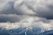 Mount Washington engulfed in storm clouds from the summit of Middle Sugarloaf Mountain in Bethlehem, New Hampshire USA during the spring months. The tracks of the Mount Washington Cog Railroad can be seen in the foreground.
