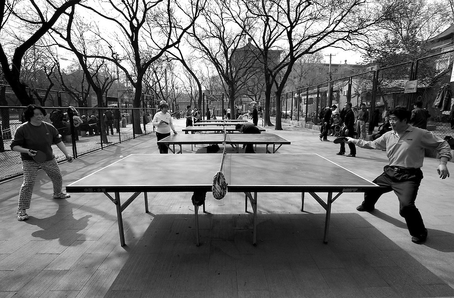 Neighborhood residents play table tennis in a Beijing Park.