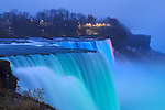 The American Falls lit by colored lights on a rainy, foggy winter evening at Niagara Falls, New York State, USA