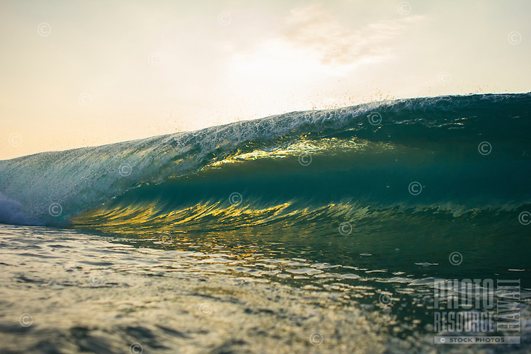 Beautiful morning light shines through a breaking wave at Sandy Beach, O'ahu.