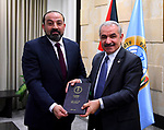Palestinian Prime Minister Mohammad Ishtayeh receives the annual report of the Public Prosecution of 2018 from the attorney general Akram al-Khatib, at his headquarter in the West Bank city of Ramallah, April 22, 2019. Photo by Prime Minister Office