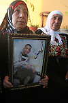 The mother of Ayman al-Abbasi, mourns as she holds her son's picture at her house in Ras al-Amoud neighborhood, in Jerusalem on November 30, 2015. A 17-year-old Palestinian youth, Ayman Al-Abbassi, was was shot with a live round in his chest on Sunday night in a clash in East Jerusalem, the Palestinian health ministry reported. Photo by Mahfouz Abu Turk