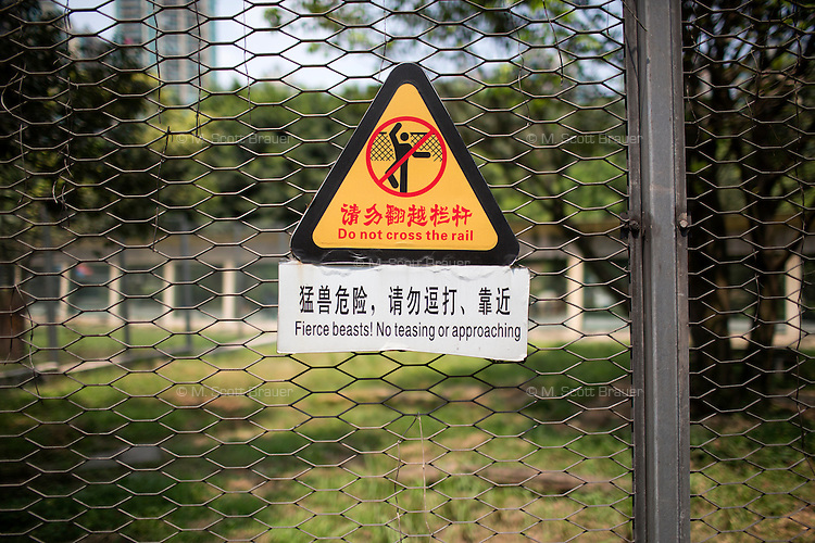 """A sign on the tiger enclosure at the Chongqing zoo warns visitors to stay away from the cage, stating """"Fierce beasts! No teasing or approaching."""" in Chongqing, China."""
