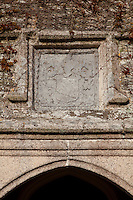 A weathered tablet depicting the Prideaux crest above the main entrance