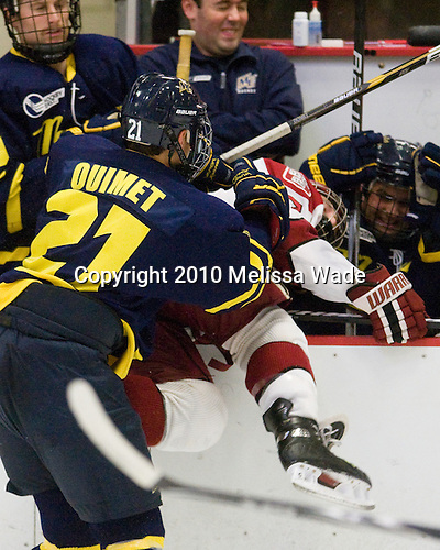Francois Ouimet (Merrimack - 21) puts Danny Fick (Harvard - 7) into the Merrimack bench. - The visiting Merrimack College Warriors defeated the Harvard University Crimson 3-1 (EN) at Bright Hockey Center on Tuesday, November 30, 2010.