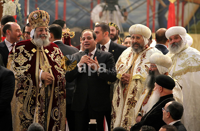 Egyptian President Abdel Fattah el-Sisi waves to the worshipers during his visit to the St. Mark's Coptic Orthodox Cathedral on the eve of the orthodox Christmas mass led by Egyptian Coptic Pope Tawadros II in Cairo on January 6, 2016. Photo by Stringer