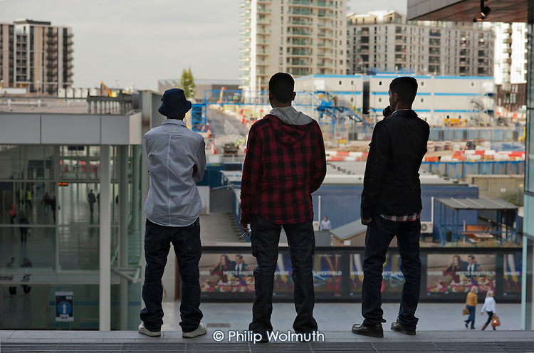 Young men look out over the Olympic construction site from Westfield Stratford City, the largest urban shopping centre in Europe. The new retail complex will be the gateway to the London 2012 Olympic Park. 2,000 of the 10,000 permanent jobs at the centre have gone to the local unemployed.