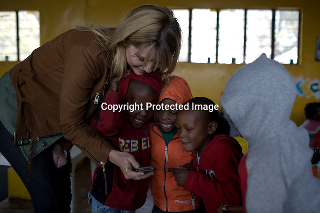 ALEXANDRA, SOUTH AFRICA - SEPTEMBER 2: Mischa Barton, the actress and model, interacts with children at Hlayisanani Pre-School on September 2, 2008 in Alexandra, outside Johannesburg, South Africa. Mischa Barton spent 2 days visiting Save The Children supported projects in South Africa, meeting school children and young children. Save The Children are helping about 51,000 children made by HIV/AIDS and poverty to access food, healthcare, social security and education. (Photo by Per-Anders Pettersson/Getty Images For Save The Children).