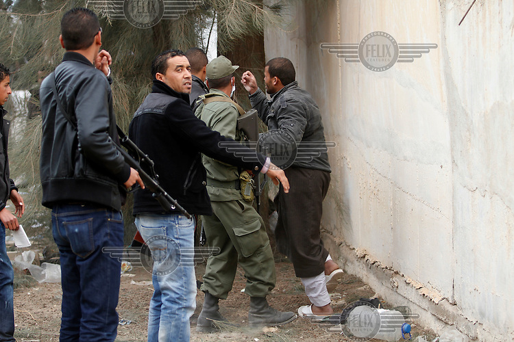 An egyptian man is caught by Tunsiian police and military after climbing the wall at the border. Tens of thousands of people, mainly Egyptian workers, flee unrest in Libya and cross the border into Tunisia. Some slept in the open for several days before being processed.  At the same time forces loyal to Col. Gaddafi fought opposition forces in various parts of the country.