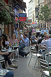 People sitting at tables of outdoor cafe, Leicester Square, London, England