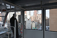A tram operator guides the newly renovated Roosevelt Island Tram out of the Manhattan station, with East side buildings in the background.