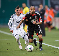 Kyle Porter (19) of D.C. United sprints past Russell Teibert (31) of the Vancouver Whitecaps during a Major League Soccer match at RFK Stadium in Washington, DC. D.C. United lost to the Vancouver Whitecaps, 1-0.