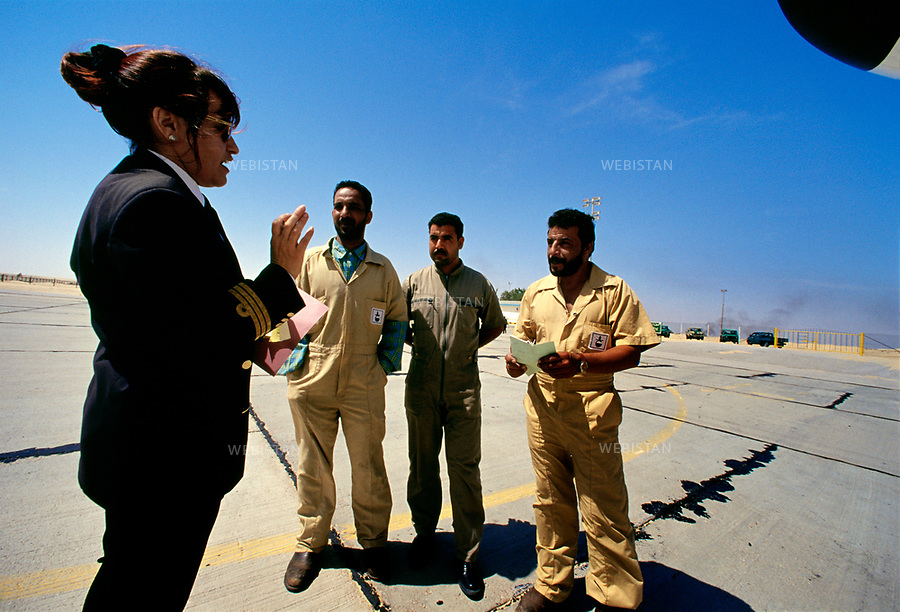 2000. Libya. Tripoli. On the landing runway of the airport, Aysh Gammo, the first female Libyan civil airplane pilot, give instructions to technicians. Libye. Tripoli. Sur la piste d'atterrissage de l'aéroport, Aysh Gammo, la première femme libyenne pilote d'avion civil, donne ses instructions à des techniciens.