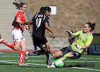 Marta of Gold Pride dribbles the ball away from Freedom's goalkeeper Erin Mcleod before scoring a goal during the second half of the game at Pioneer Stadium in Hayward, California.  Gold Pride defeated Washington Freedom, 3-2.