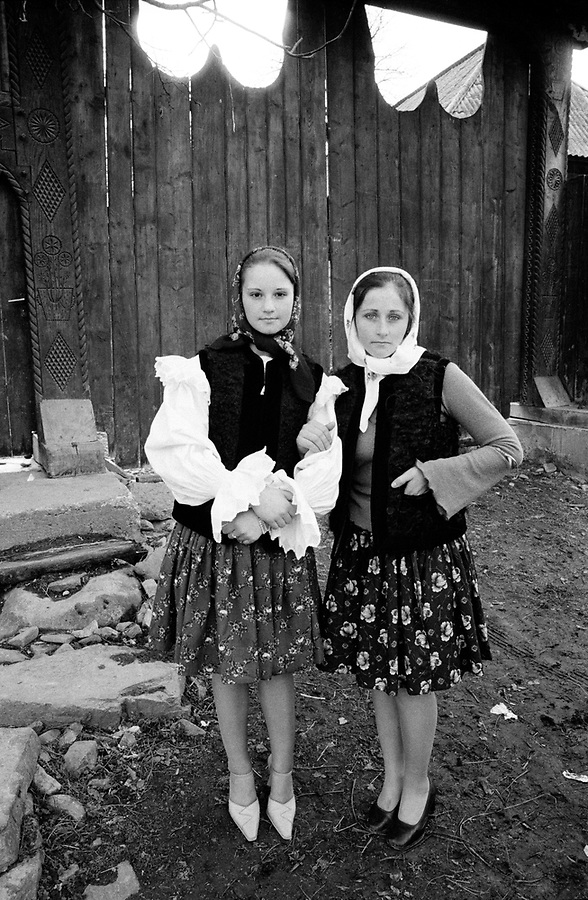 ROMANIA / Maramures / Valeni / April 2003..Teenage girls pose in front of a wooden gate on Easter Sunday. Maramures is famous for its intricately carved gates guarding each family compound...© Davin Ellicson / Anzenberger