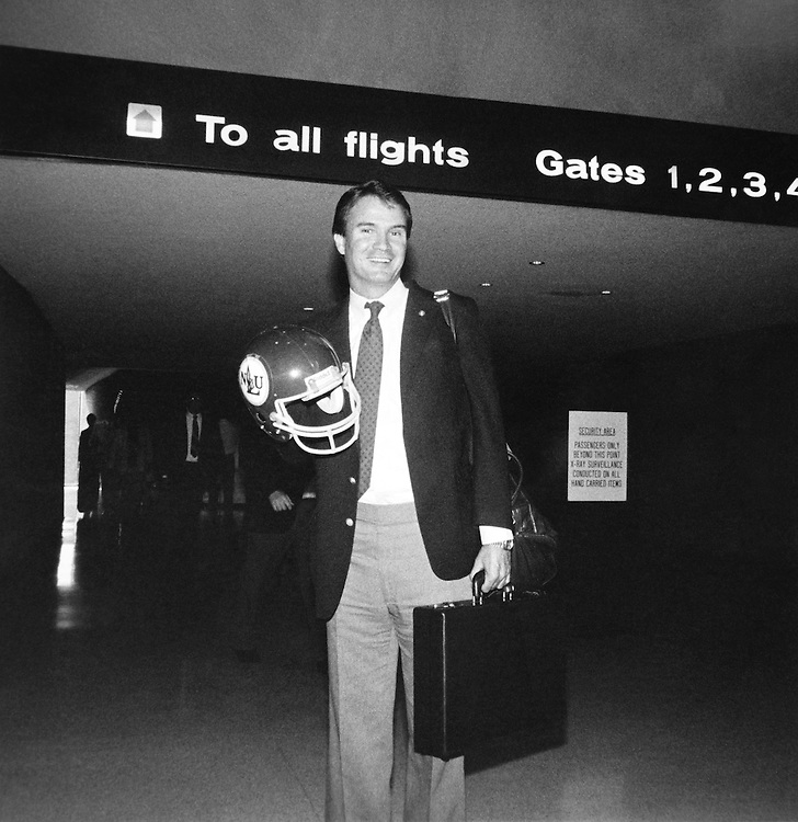 Rep. John Berlinger Breaux, D- La., United States Senator, standing with helmet and briefcase at airport. (Photo by CQ Roll Call)