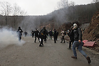 Skouries, Greece Sunday 23 November 2014<br /> Pictured: Protesters move back<br /> Re: Riot police called to break up a protest by local residents against a Canadian-run goldmine in Skouries, in the Chalkidiki area. Eldorado firm has been accused of dumping toxic waste generated during gold processing in northern Greece, into local rivers. Teargas was used by the police to disperse the protesters who retaliated with pyrotechnics.