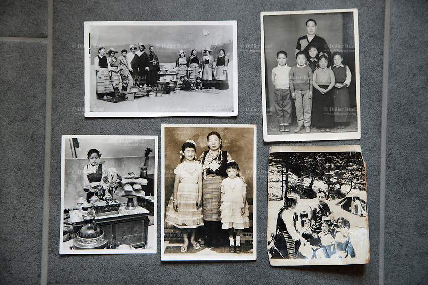 """Switzerland. Canton Aargau. Brugg. Yangchen Büchli and black and white pictures from her childhood in Tibet. On the bottom right corner, the picture shot before her departure and depicting her as child with the young Dalai Lama. The swiss tibetan woman is an Aeschimann's child who arrived 50 years ago in Switzerland to receive custody on a private initiative by an influential Swiss industrialist, Charles Aeschimann. In 1962, Charles Aeschimann agreed with the Dalai Lama to take 200 children and place them in Swiss foster homes and give them a chance for a better life and a good education. Most of the children still had parents in exile or in Tibet, just a few were orphans. The 14th and current Dalai Lama is Tenzin Gyatso, recognized since 1950. He is the current Dalai Lama, as well as the longest-lived incumbent, well known for his lifelong advocacy for Tibetans inside and outside Tibet. Dalai Lamas are amongst the head monks of the Gelug school, the newest of the schools of Tibetan Buddhism. The Dalai Lama, also called """" Ocean of Wisdom"""" is considered as the incarnation of Chenresi, the Bodhisattva of compassion who is also the protective deity of Tibet. 25.02.2015 © 2015 Didier Ruef"""