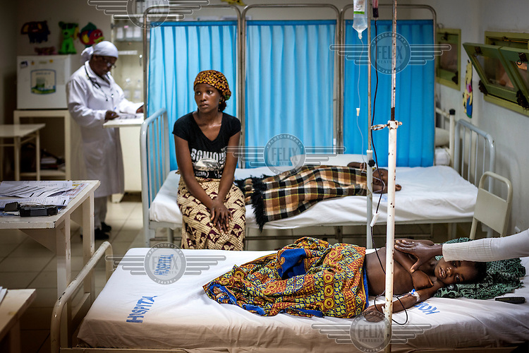 A mother sits at the bedside of her child in the Manhisa hospital.