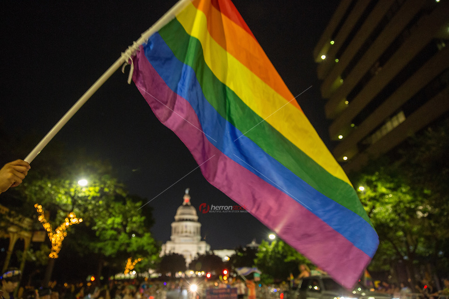 AUSTIN, TEXAS - A rainbow flag towers over the State of Texas Capitol Dome at the 2016 Austin PRIDE Parade on Saturday, Aug. 27, 2016. <br /> <br /> Use of this image in advertising or for promotional purposes is prohibited.<br /> <br /> Editorial Credit: Dan Herron / Herronstock Editorial.