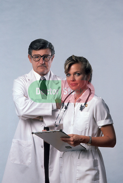 portrait of stern doctor and nurse against white background
