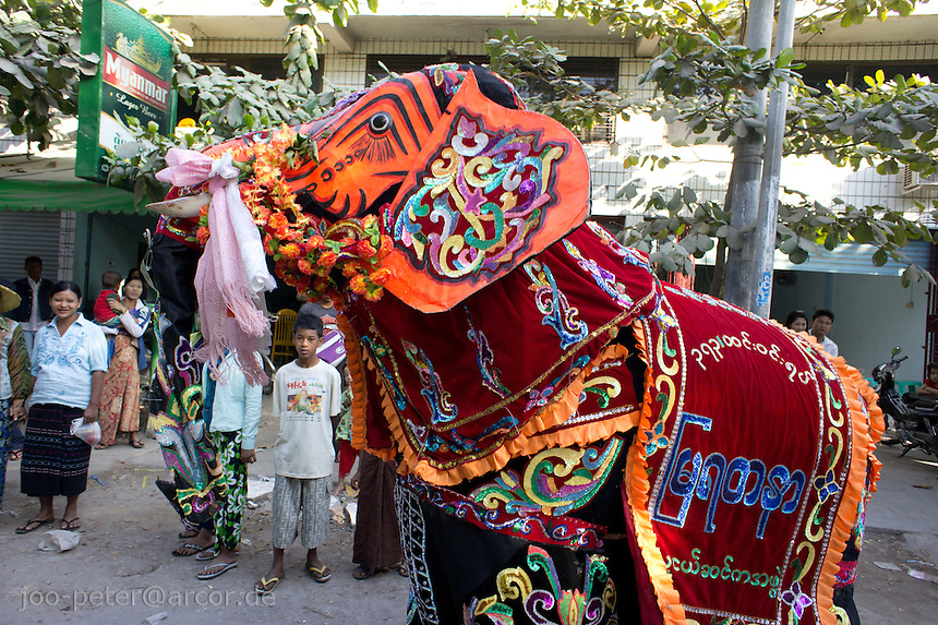 performer in elephant  costume in a small street parade,  Mandalay, Myanmar, 2011