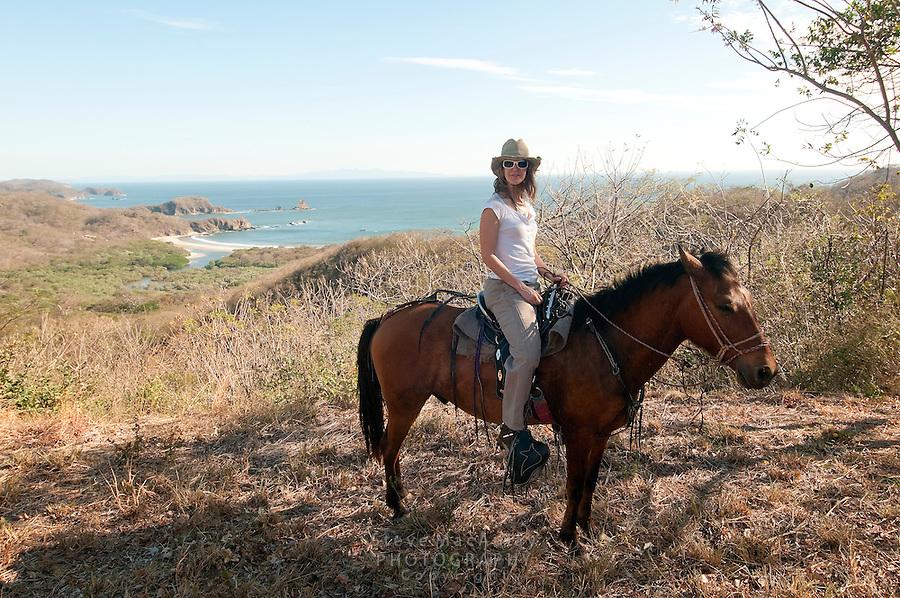 Young woman on horseback on bluff above beach. Morgan's Rock Hacienda and Eco Lodge, Nicaragua