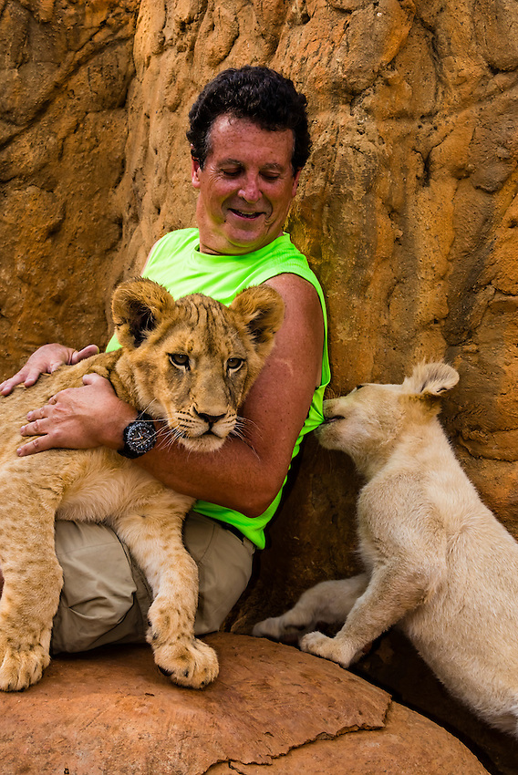 Blaine Harrington with a 4 month old Lion Cub and a 2 month old White Lion cub, Lion Park, near Johannesburg, South Africa.