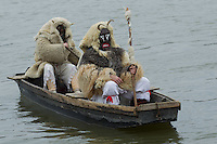 Local people in traditional buso dresses cross river Danube to celebrate the Buso Carnival in Mohacs, about 200 km south from the capital city Budapest on March 02, 2014. ATTILA VOLGYI