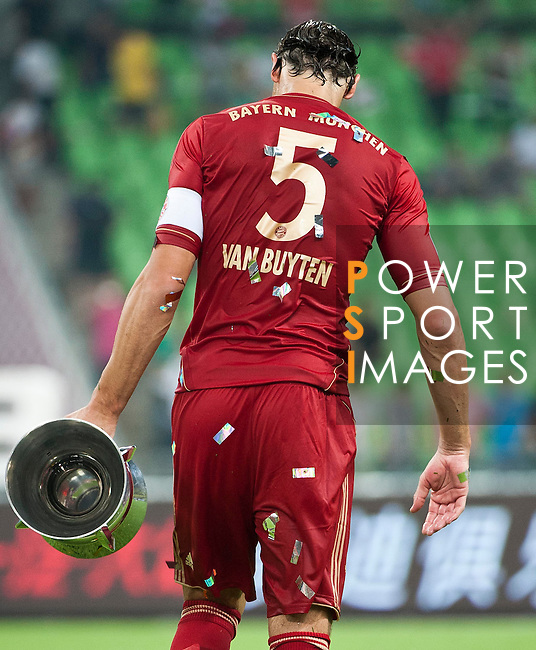 GUANGZHOU, GUANGDONG - JULY 26:  Daniel Van Buyten of Bayern Munich carries the trophy after winning a friendly match against VfL Wolfsburg as part of the Audi Football Summit 2012 on July 26, 2012 at the Guangdong Olympic Sports Center in Guangzhou, China. Photo by Victor Fraile / The Power of Sport Images