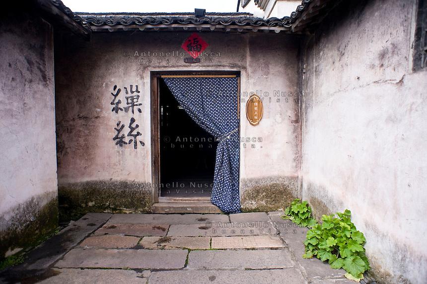 L'entrata di una vecchia fabbrica della seta.<br /> Wuzhen &egrave; una piccola citt&agrave; della provincia dello Zhejiang chiamata anche la Venezia d'Oriente per la caratteristica dei canali che corrono lungo i vicoli dell'antica citt&agrave;. E' anche riconosciuta come uno dei centri pi&ugrave; importanti per la produzione e la lavorazione della seta nell'antichit&agrave;. Ancora sono presenti alcune piccole ditte che continuano a lavorare la seta con gli stessi metodi di come si faceva da secoli. Nonostante sia diventata una meta turistica ancora si pu&ograve; respirare la vecchia Cina nel modo di vivere dei cittadini e nel percorrere i vecchi vicoli costruiti con la pietra e rimasti intatti nei secoli.