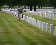 May 23, 2013  (Arlington, Virginia)  Staff Sgt. Troy Paolantonio, of the 3rd U.S. Infantry Regiment (the Old Guard), places an American flag before a gravestone at Arlington National Cemetery. The annual tradition, known as Flags In, honors every fallen soldier's grave with a flag.  (Photo by Don Baxter/Media Images International)
