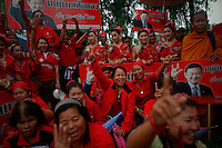 "Supporters hold pictures of ousted premier Thaksin Shinawatra as they celebrate branding as red the village of Suan Mon near Udon Thani in northeastern Thailand June 25, 2011. Regional leaders of Thailand's red-shirt protest movement held traditional Buddhist ceremony to launch 38 villages designated as ""Red Shirt Village of Democracy."" The red shirts, supporters of ousted premier Thaksin Shinawatra, have been branding hundreds of villages as red to rally behind Thaksin's sister, Yingluck, who is leading the opposition ahead of July 3 general elections.   REUTERS/Damir Sagolj (THAILAND)"