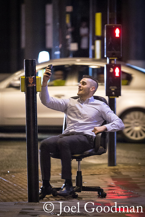 © Joel Goodman - 07973 332324 . 21/12/2013 . Manchester , UK . A man spins on an office chair in the street as he records himself on his mobile phone . Christmas revellers out in the rain in Manchester on Mad Friday , the last Friday night before Christmas which is typically one of the busiest nights of the year for police and ambulance crews . Photo credit : Joel Goodman