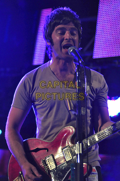 NOEL GALLAGHER of OASIS .Oasis perform on day two of the Roskilde Festival in Roskilde, Denmark, .July 3rd 2009..music concert gig band live on stage playing performing half length guitar microphone singing .CAP/TTL .©TTL/Capital Pictures