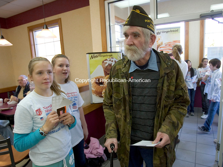 WINSTED, CT. 11 November 2010-111110SV01--From left, Kestrel Thorne, 13, vice president of the student council at Northwestern Middle School greets Gary Brown of Winsted, a member of VFW 296, during a free breakfast for veterans at Dunkin' Donuts in Winsted Thursday.<br /> Steven Valenti Republican-American