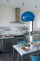The freestanding stainless steel units give this kitchen an industrial feel and the blue Kartell lamp by Ferruccio Laviani adds a splash of colour