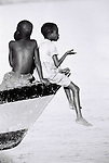 A group of children sit on a boat tethered by the shore of Lake Malawi.