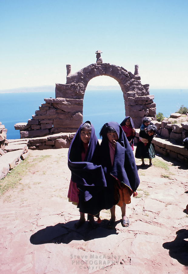 Young girls in indigo shawls at top of steps coming up from boat landing at Taquile Island, Lake Titicaca, Peru