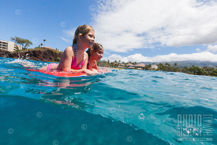 Split-level view of two girls playing in the water with their boogie board off of Maui.