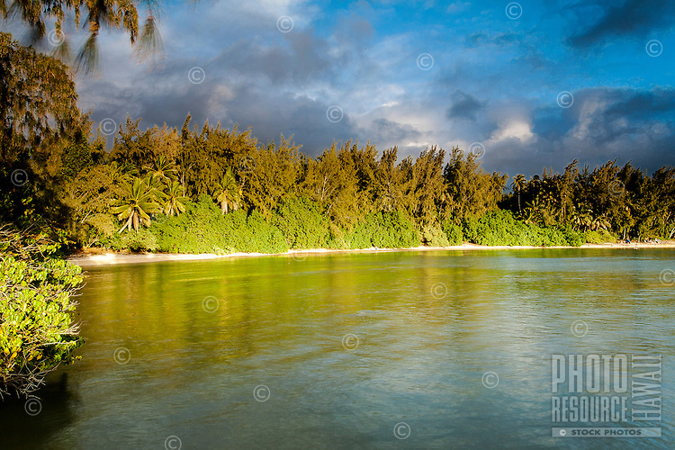 The early evening sun shining on the remote shore of Kawela Bay on the North Shore of O'ahu