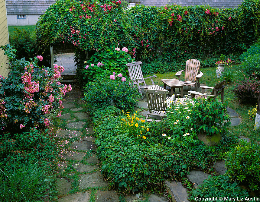 Provincetown, Cape Cod, MA <br /> Secluded summer garden with stone pathway and a grouping of Adirondack chairs
