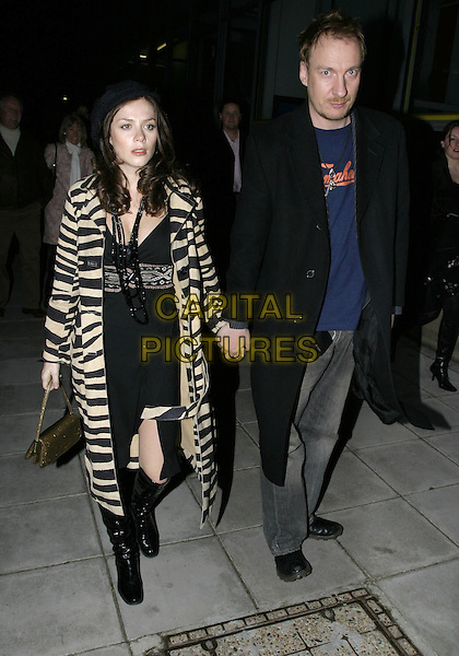 "ANNA FRIEL & DAVID THEWLIS.Leaving performance of ""Drallion"", Cirque du Soleil, Royal Albert Hall, London, January 6th 2005..full length boyfriend girlfriend couple gold bag zebra striped coat black and white stripes animal print knee high black boots dress holding hands.Ref: AH.www.capitalpictures.com.sales@capitalpictures.com.©Capital Pictures."