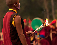 Buddhist Monk lighting incense sticks for the Losar ceremony