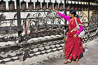 Kathgmandu, Nepal.  Nepali Woman Spinning Prayer Wheels at Swayambhunath Temple.
